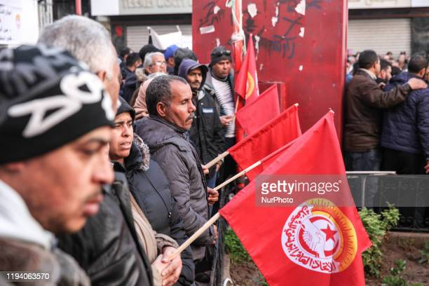 Unionists hold flags of the UGTT labor union as they attend a gathering held outside the UGTT headquarters in Tunis to celebrate the 9th anniversary...