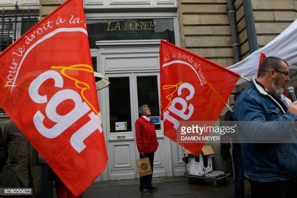 CGT union's flags are seen in front of an office of French postal service company La Poste as postmen on strike demonstrate against the...