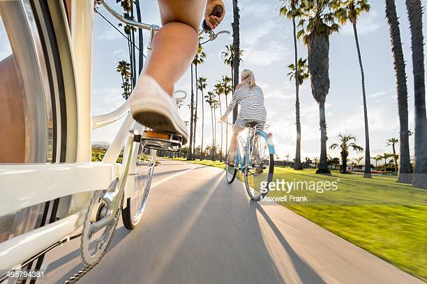 a unique angle of two women riding their bikes down the bike path on the beach. this rig shot gives a sense of speed and a fresh perspective on cycling. - santa barbara stock photos and pictures