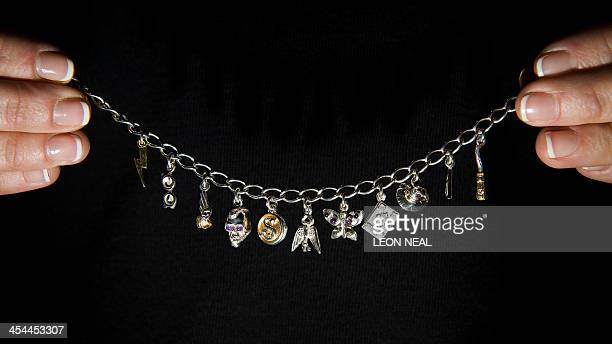 A unique personal charm bracelet based on designs by J K Rowling is shown at the Sotheby's auction house in central London on December 9 2013...