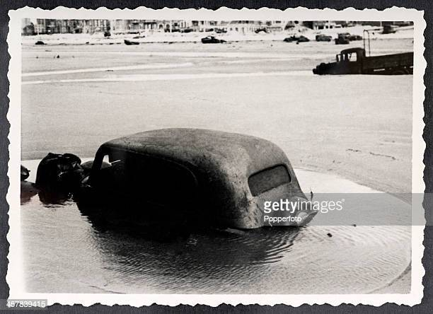 A unique snapshot taken by a German soldier after the British withdrawal from Dunkirk in France showing motor transport abandoned on the beach during...