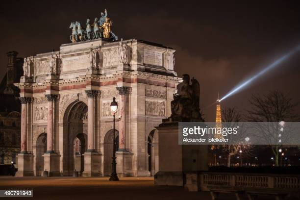 CONTENT] Unique view of the magnificent Arc de Triomphe du Carrousel at night with Eiffel Tower in the background sending out its light beacon