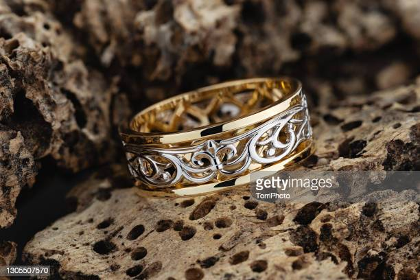 unique wedding ring with fleur de lys ornament on wood background - white gold stock pictures, royalty-free photos & images