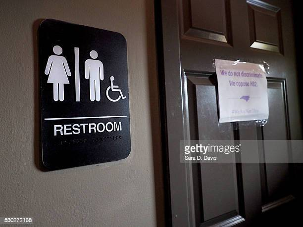 A unisex sign and the 'We Are Not This' slogan are outside a bathroom at Bull McCabes Irish Pub on May 10 2016 in Durham North Carolina Debate over...