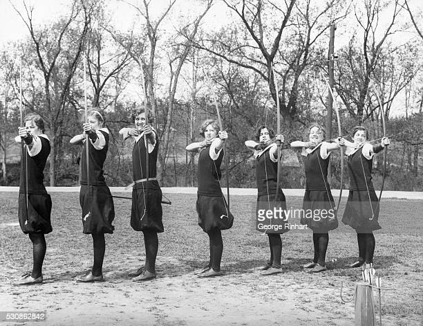 Unison in movement- seven bows drawn and arrows aimed at one target. A class in archery at Smith College, one of the world's largest schools for...