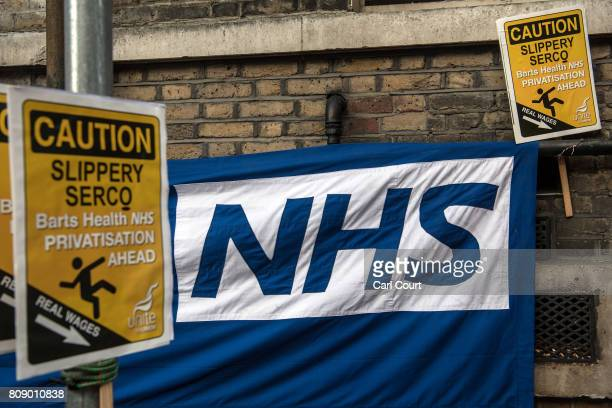 Unite union placards are placed next to an NHS logo during strike action in a dispute over job cuts pay and working conditions outside Royal London...