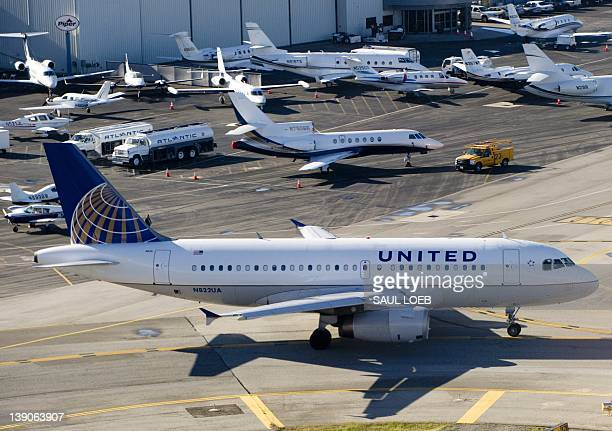 A United Airlines Airbus A319 airplane waits on a taxiway to takeoff alongside private jets at John Wayne Airport in Santa Ana California February 16...