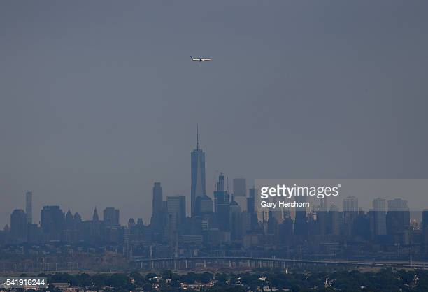 United Airlines airplane on approach to Newark Liberty Airport flies over Lower Manhattan in New York on June 18, 2016 as seen from Montclair, NJ.