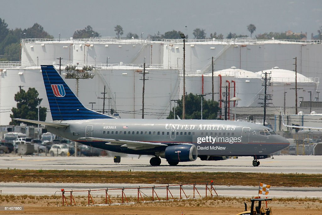 A United Airlines Boeing 737 Jet Taxis Past Fuel Storage Tanks At Los Angeles International Airport