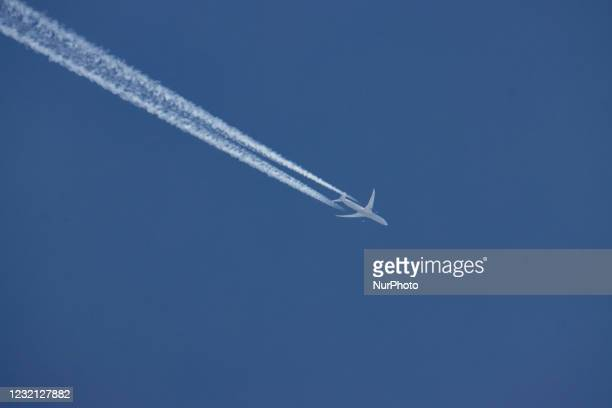 United Airlines Boeing 787 Dreamliner airplane is seen overflying in the blue sky over Amsterdam. The wide-body aircraft is a B787-10 with...