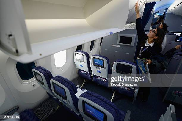 United Airlines customer service representative Desiree Yoos looks at the storage bins while touring the new Boeing 787 Dreamliner at Los Angeles...