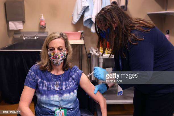 United Airlines employee Jenifer Cienkus receives a COVID-19 vaccine at United's onsite clinic at O'Hare International Airport on March 09, 2021 in...