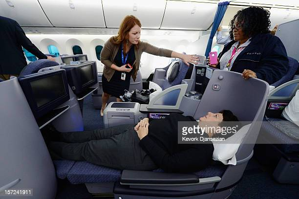 United Airlines employee Jennifer Dohm helps United sales manager Marilyn Jablonsky with the lighting as a flight attendant looks on while they tour...