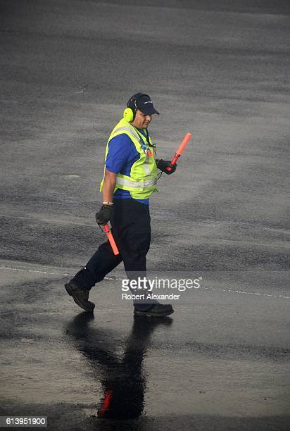 A United Airlines ground crew member prepares to guide a passenger plane to its gate at LaGuardia Airport in the New York City borough of Queens on...