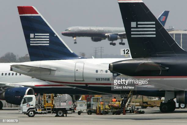 United Airlines jet lands as US Airways jets are prepared for flight at Los Angles International Airport July 17, 2008 in Los Angles, California. The...