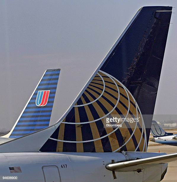 United Airlines jet with the company's logo visible on its tail fin taxis past a Continental Airlines jet parked at a gate at O'Hare International...