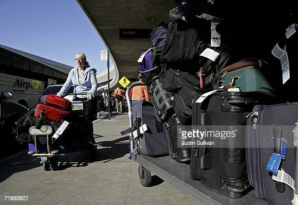 United Airlines passenger pushes her baggage past piles of luggage at San Francisco International Airport August 11 2006 in San Francisco The...