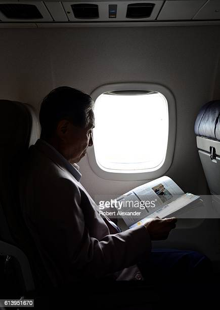 A United Airlines passenger reads a magazine as the plane departs Denver International Airport in Denver Colorado