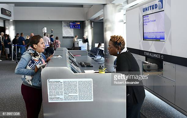 A United Airlines passenger traveling with her pet dog talks to an airline agent at a boarding gate at Denver International Airport
