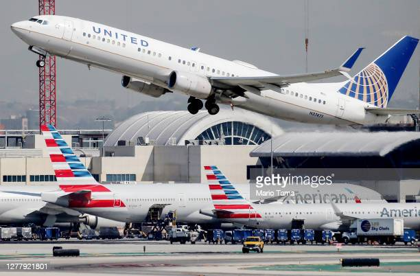 United Airlines plane takes off above American Airlines planes on the tarmac at Los Angeles International Airport on October 1, 2020 in Los Angeles,...
