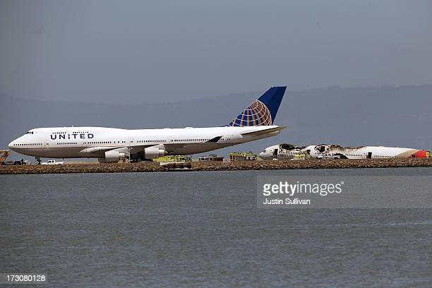 United Airlines plane taxis on the runway as a Boeing 777 airplane lies burned after it crashed landed at San Francisco International Airport July 6...