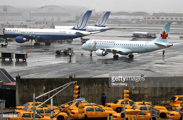 United and Air Canada jets seen through rain and fog sit on the tarmac as taxis wait in traffic at John F Kennedy International Airport in New York...