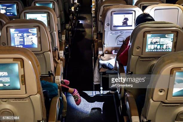 United Arab Emirates Abu Dhabi International Airport onboard cabin economy class Etihad Airways flight girl sleeping feet dangling