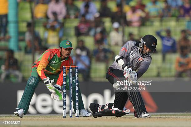 United Arab Emirates batsman Khurram Khan plays a shot as Bangladesh wicketkeeper Anamul Haque looks on during the ICC T20 World Cup warmup cricket...