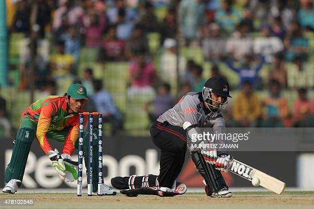 United Arab Emirates batsman Khurram Khan plays a shot as Bangladesh wicketkeeper Anamul Haque looks on during the ICC T20 World Cup warm up cricket...
