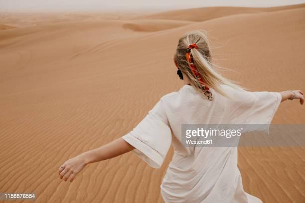 united arab emirates, dubai, lahbab desert, woman walking in desert landscape - dubai stock pictures, royalty-free photos & images