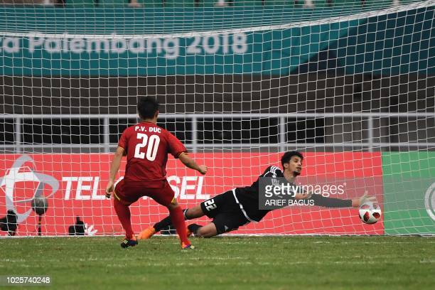 United Arab Emirates' goalkeeper Mohamed Alshamsi tries to make a save from Vietnam's Phan van Duc during the penalty shootouts in the men's bronze...