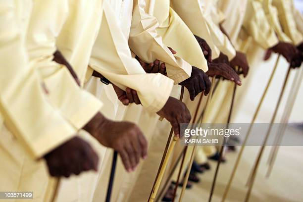 United Arab Emirati men hold canes as they perform a local traditional Bedouin folklore dance during the fourth Liwa Date Festival 2010 in of Abu...