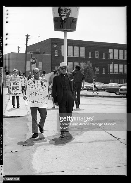 United Farm Workers protesters including Monsignor Charles Owen Rice carrying signs reading 'Colonel Sanders Unfair to Farm Workers' outside Kentucky...
