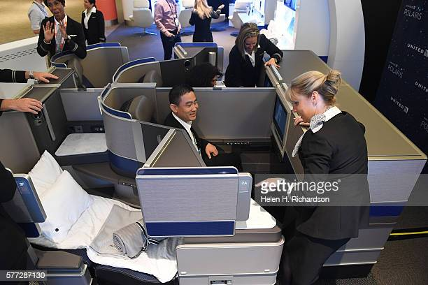 United flight attendant Treece ReynoldsMilbaum right shows Business traveler Henry Hu middle some of the amenities available on the new United...