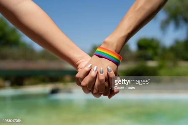 united hands of woman with lgtbi bracelet - bisexuality fotografías e imágenes de stock
