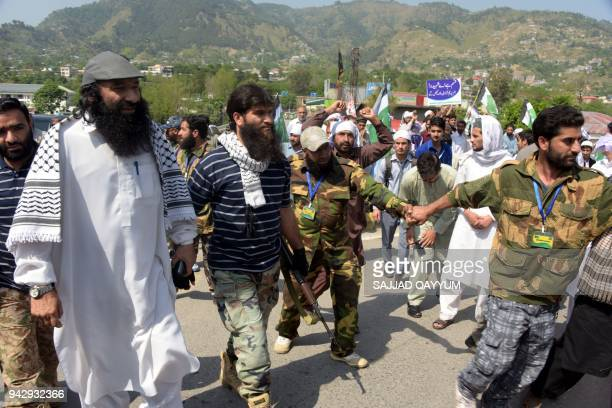 United Jihad Council leader Syed Salahuddin walks with activists and supporters during a protest against the recent violence in Indianadministered...