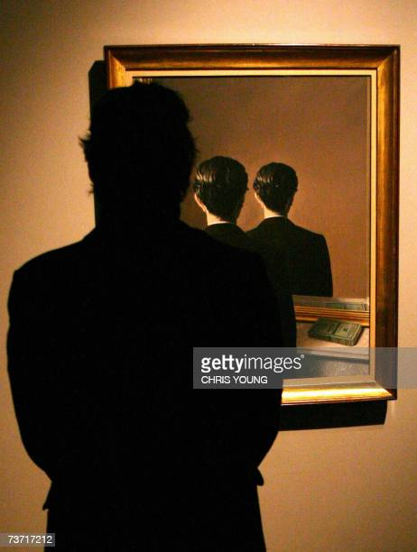 A man looks at Rene Magritte's 'La Reproduction' painting at the 'Surreal Things' exhibition press preview in London's Victoria and Albert Museum 27...
