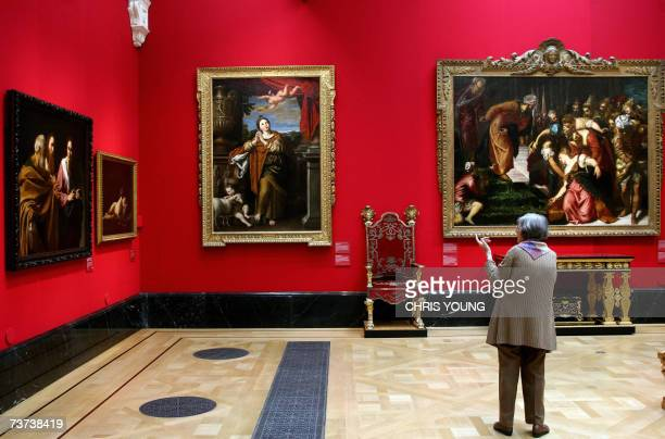 United Kingdom: A visitor examines Caravaggio's 'The Calling of Saints Peter and Andrew' as it hangs Giovanni Battista Caracciolo's 'Cupid Sleeping'...
