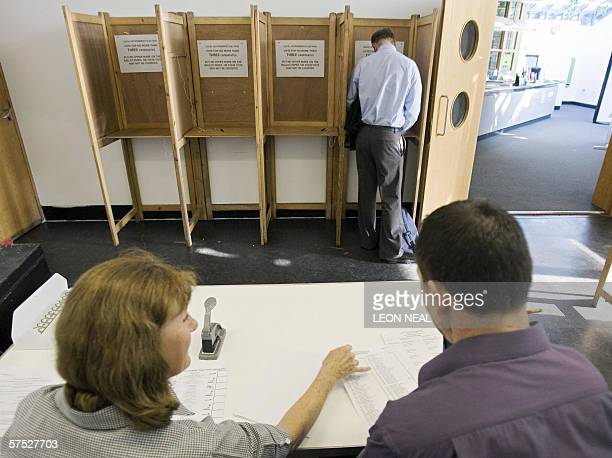 A voter marks his voting card in a polling station as election officials look on at a polling station in Wandsworth in south London 04 May 2006...