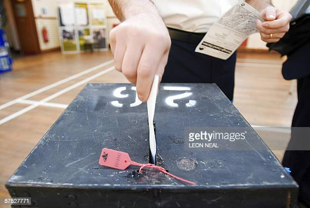 A voter places his voting card into a ballot box at a polling station in Wandsworth in southLondon 04 May 2006 during local government elections in...