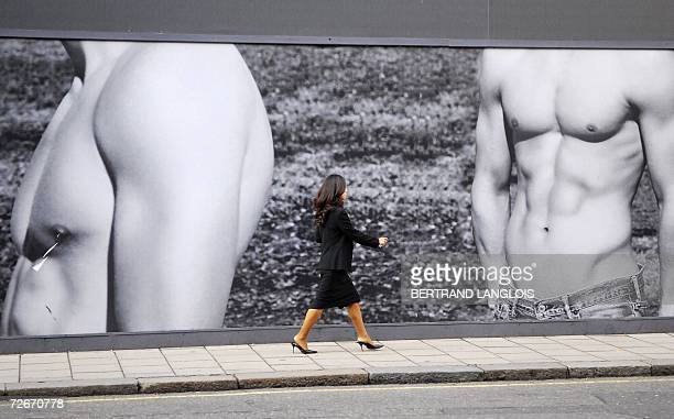 A woman walks past an advertising billboard in central London 29 november 2006 AFP PHOTO/BERTRAND LANGLOIS