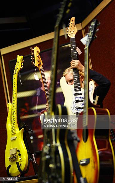 An Christie's employee holds a guitar during a press preview of a pop memorabilia sale at Christie's auction house in London 29 April 2005 Guitars...