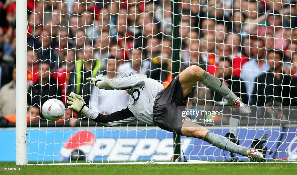 Arsenal's Jens Lehmann blocks the penalty kick of Paul Scholes during their FA Cup Final football match at the Millennium Dome in Cardiff, Wales, 21 May, 2005. The teams tied 0-0 with Arsenal winning 5-4 on penalties. AFP PHOTO/ADRIAN DENNIS No telcos, website uses subject to subscription of a license with FAPL on www.faplweb.com <http://www.faplweb.com>