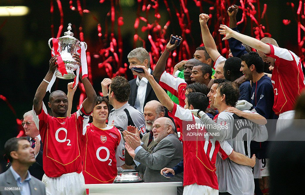Arsenal's Patrick Vieira (L) lifts the FA Cup as he celebrates with his teammates winning the FA Cup Final football match against Manchester United at the Millennium Dome in Cardiff, Wales, 21 May, 2005. The teams tied 0-0 with Arsenal winning 5-4 on penalty kicks. AFP PHOTO/ADRIAN DENNIS No telcos, website uses subject to subscription of a license with FAPL on www.faplweb.com <http://www.faplweb.com>
