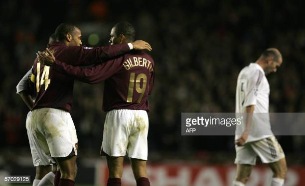 Arsenal's Thierry Henry Gilberto celebrate as Real Madrid's Zinedine Zidane walks from the pitch after Arsenal eliminated Real Madrid from the...