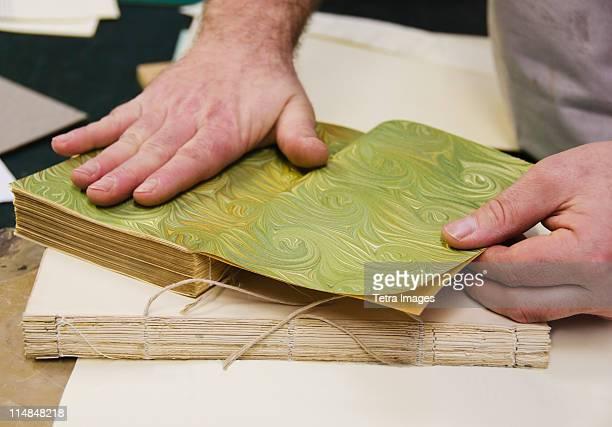 United Kingdom, Bristol, hands binding book