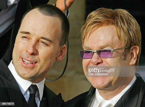 British pop singer Sir Elton John with his partner David Furnish pose for photographs at the Guildhall in Windsor 21 December 2005 after conducting a...