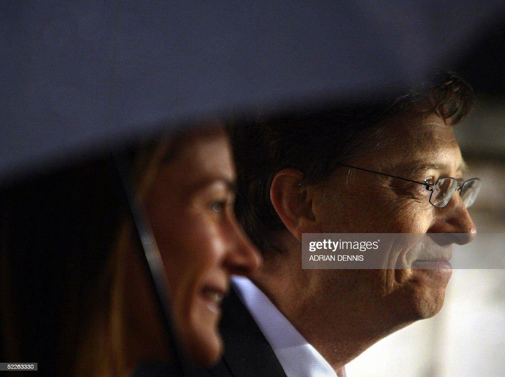 Chairman and Chief Software architect of Microsoft Bill Gates and his wife Melinda stand beneath an umbrella after he received an honorary knighthood at Buckingham Palace in London 02 March 2005. Gates was presented with the honor by Her Majesty Queen Elizabeth in recognition of Gates' contributions to improving health and reducing poverty in parts of the Commonwealth and elsewhere in the developing world. Gates was also recognised for his contribution to enterprise, employment, education and the voluntary sector in the United Kingdom.