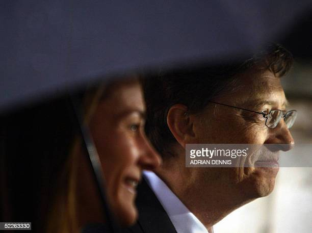 United Kingdom: Chairman and Chief Software architect of Microsoft Bill Gates and his wife Melinda stand beneath an umbrella after he received an...