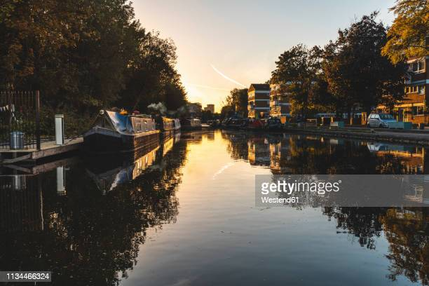 united kingdom, england, camden, london, regent's canal, house boats at sunset - camden london stock pictures, royalty-free photos & images